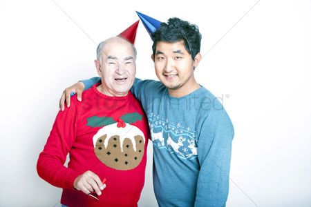 Excited : Portrait of a senior adult man and a young asian man wearing christmas jumpers and party hats