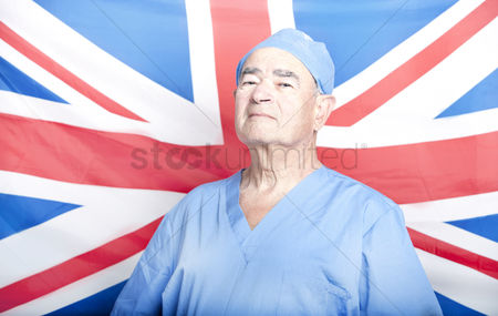 British ethnicity : Portrait of a senior adult surgeon in front of a british flag