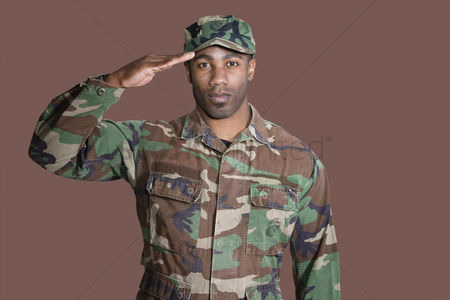 Respect : Portrait of a young african american us marine corps soldier saluting over brown background