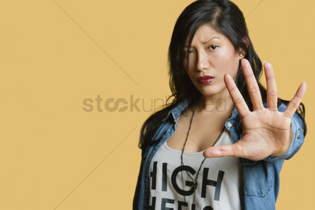 Jacket : Portrait of a young woman gesturing stop sign over colored background