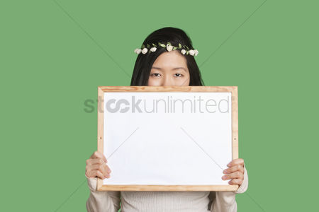 Shyness : Portrait of a young woman hiding her face with a blank whiteboard over green background