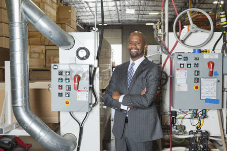 Bald : Portrait of african american businessman standing arms crossed with machinery in background