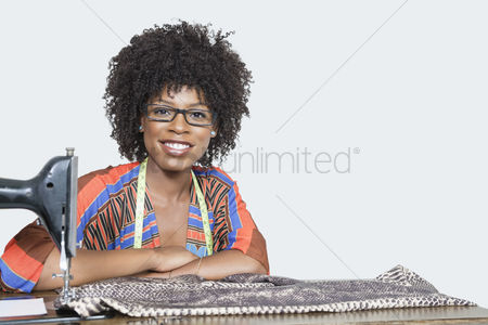 Traditional clothing : Portrait of an african american female fashion designer with sewing machine and cloth over gray background
