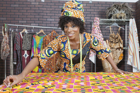 Traditional clothing : Portrait of an african american female fashion designer working on a pattern cloth