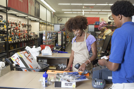 Supermarket : Portrait of an african american female store clerk standing at checkout counter scanning item serving male customer