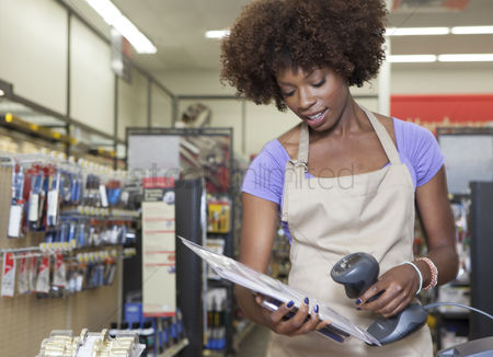 Three quarter length : Portrait of an african american female store clerk standing at checkout counter scanning item