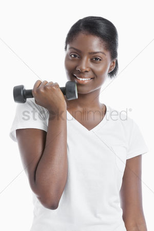 Dumbbell : Portrait of an african american young woman with dumbbell over white background