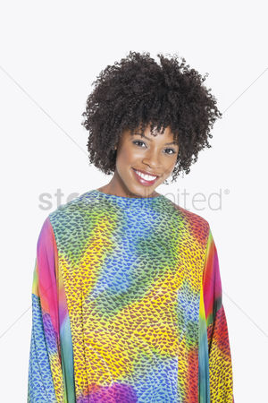 Traditional clothing : Portrait of an attractive african american woman in multicolored dashiki standing over gray background