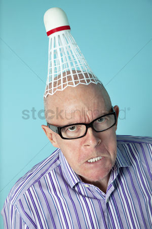 Funny : Portrait of angry senior man with shuttlecock on head over colored background