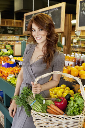 Supermarket : Portrait of beautiful brunette with basket shopping in market