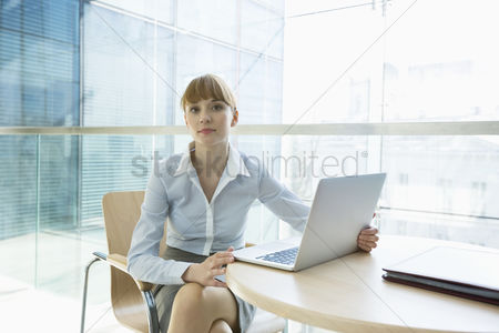 Three quarter length : Portrait of beautiful businesswoman with laptop sitting at table in office