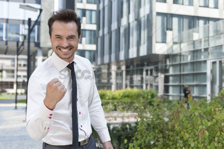 Businessmen : Portrait of cheerful businessman with clenched fist standing outside office building