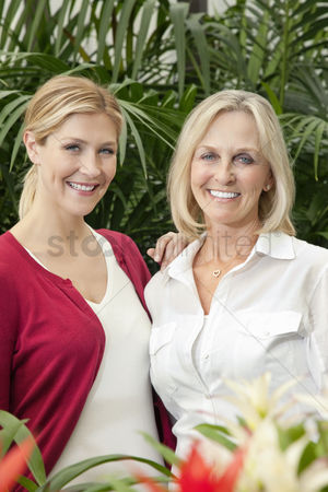 Greenhouse : Portrait of cheerful mother and daughter in garden