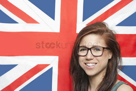 British ethnicity : Portrait of cheerful young woman wearing eyeglasses against british flag
