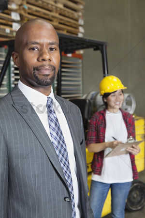 Forklift : Portrait of confident african american male businessman with female worker standing in background