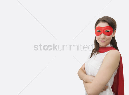 Young woman : Portrait of confident businesswoman dressed as superhero standing arms crossed in office