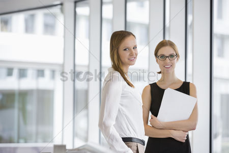 Office worker : Portrait of confident businesswomen with documents in office