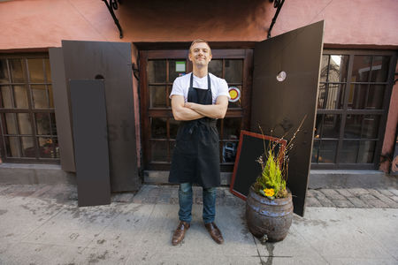 Apron : Portrait of confident male salesperson standing arms crossed outside coffee store