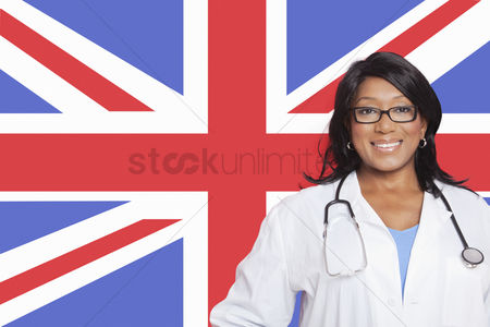 Respect : Portrait of confident mixed race female surgeon over british flag
