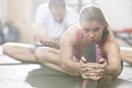 Two people : Portrait of confident woman doing stretching exercise in crossfit gym