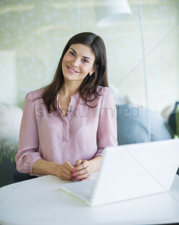 Office worker : Portrait of confident young businesswoman with laptop at office table