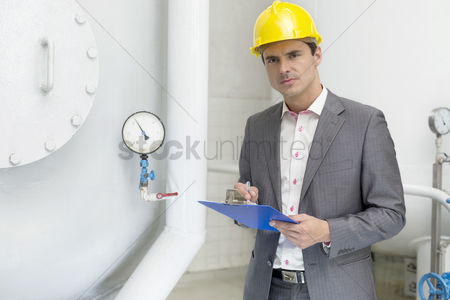 Supervisor : Portrait of confident young male inspector writing on clipboard in industry