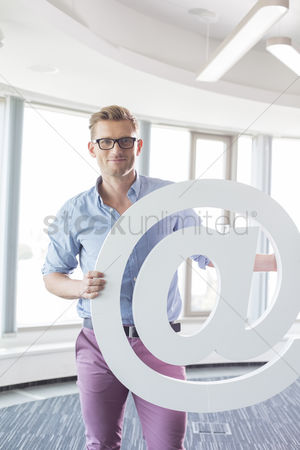 Internet : Portrait of creative businessman holding at sign in office