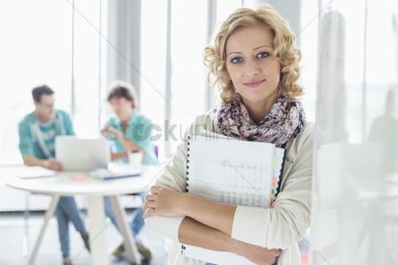 Smiling : Portrait of creative businesswoman holding files with colleagues working in background at office