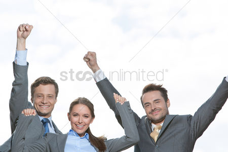 Celebrating : Portrait of excited businesspeople with arms raised on terrace against sky