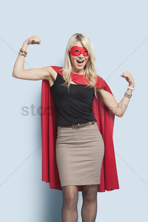 Background : Portrait of excited young blond woman in superhero costume flexing arms over light blue background