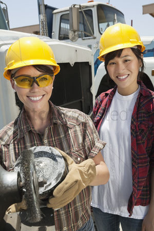 Land : Portrait of female industrial worker buffing a truck engine cylinder with coworker standing besides her