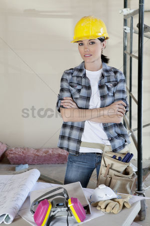 Earphone : Portrait of female worker standing with arms crossed at construction site