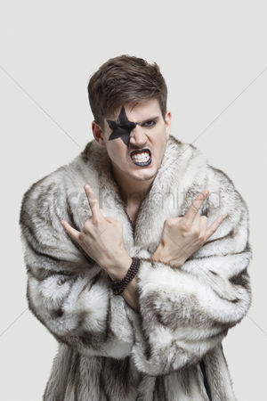 Rage : Portrait of frustrated young man in fur coat clenching teeth and making rebellious gesture against gray background