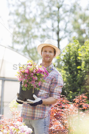 Greenhouse : Portrait of gardener holding flower pot outside greenhouse
