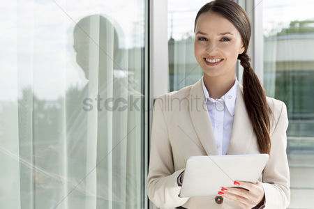 Business suit : Portrait of happy businesswoman using digital tablet by glass door