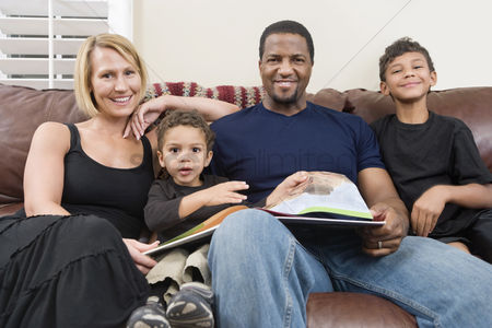 Husband : Portrait of happy family sitting on sofa