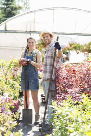 Greenhouse : Portrait of happy gardeners standing outside greenhouse