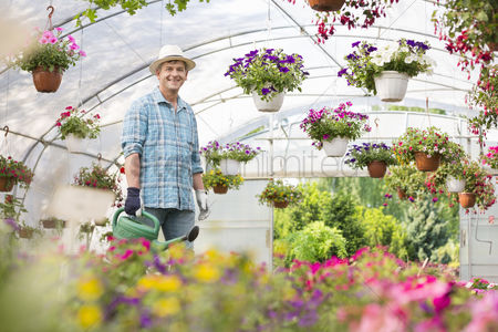 Greenhouse : Portrait of happy man carrying watering can in greenhouse