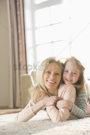 Pre teen : Portrait of happy mother and daughter lying on floor at home