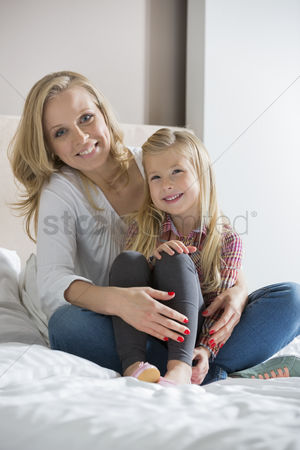 Sitting on lap : Portrait of happy mother and daughter sitting on bed at home
