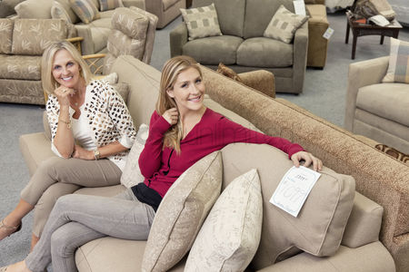 Furniture : Portrait of happy mother and daughter sitting on sofa in furniture store