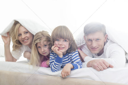 Children : Portrait of happy parents and children lying under bed cover