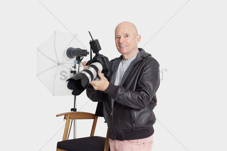 Bald : Portrait of happy senior man with camera standing in photographer s studio