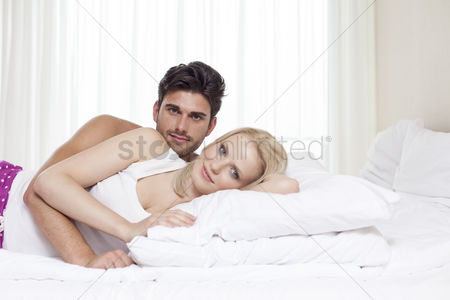 Couples : Portrait of happy young couple lying in bed