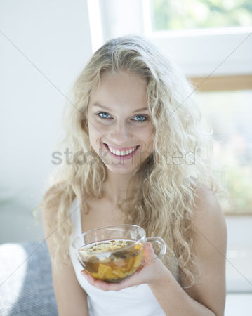 Czech republic : Portrait of happy young woman holding herbal tea cup in house