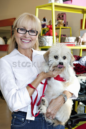 Large group of animals : Portrait of pet shop owner carrying dog
