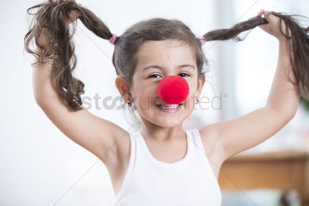 Czech republic : Portrait of playful little girl wearing clown nose holding pigtails at home