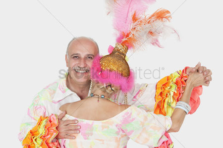 Dancing : Portrait of senior couple in brazilian outfits dancing over gray background