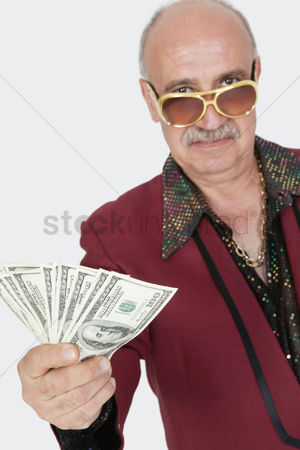 Man suit fashion : Portrait of senior man showing us banknotes against gray background