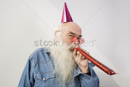 Bald : Portrait of senior man wearing party hat while blowing horn against gray background